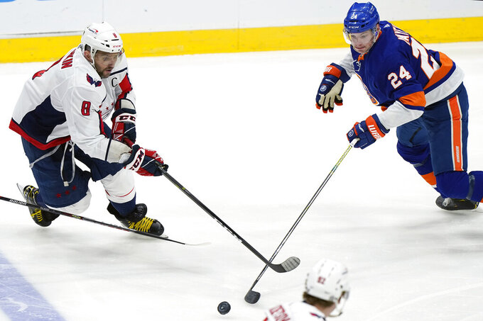 New York Islanders defenseman Scott Mayfield (24) and Washington Capitals left wing Alex Ovechkin (8) go after the puck during the second period of an NHL hockey game Thursday, April 22, 2021, in Uniondale, N.Y. (AP Photo/Kathy Willens)