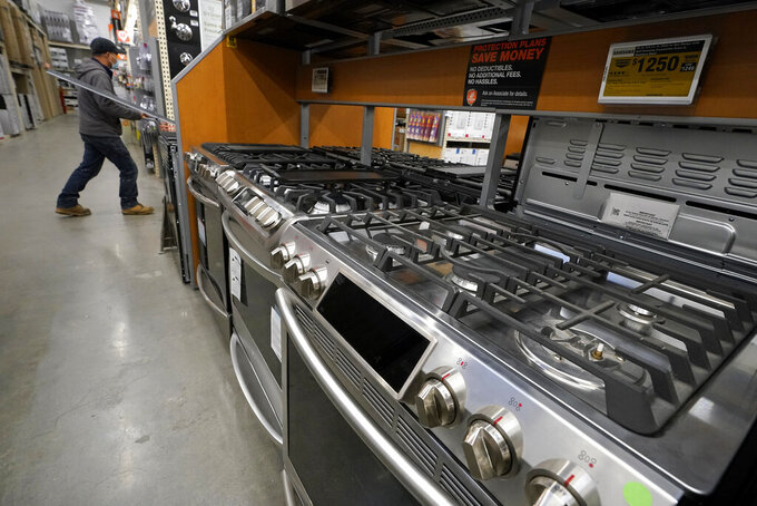 This Oct. 29, 2020 file photo, a passer-by walks past stoves on display at a Home Depot location, in Boston.  Orders to U.S. factories for big-ticket goods shot up 3.4% in January 2021, pulled up by surge in orders for civilian aircraft. A category that tracks business investment posted a more modest gain, the Commerce Department reported Thursday, Feb. 24.  .(AP Photo/Steven Senne, File)