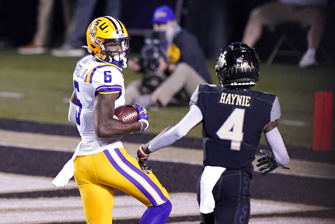 LSU wide receiver Terrace Marshall Jr. (6) looks back at Vanderbilt cornerback Randall Haynie (4) as Marshall scores a touchdown on a 51-yard pass reception in the first half of an NCAA college football game Saturday, Oct. 3, 2020, in Nashville, Tenn. (AP Photo/Mark Humphrey)