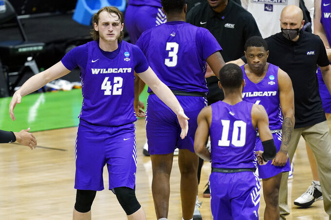 Abilene Christian's Clay Gayman (42) and Damien Daniels, right, wait to congratulate Reggie Miller (10) during a timeout in the second half of a college basketball game against Texas in the first round of the NCAA tournament at Lucas Oil Stadium in Indianapolis Saturday, March 20, 2021. (AP Photo/Mark Humphrey)