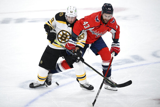 Boston Bruins left wing Brad Marchand (63) and Washington Capitals right wing Tom Wilson (43) battle for the puck during the first period of an NHL hockey game, Saturday, Jan. 30, 2021, in Washington. (AP Photo/Nick Wass)