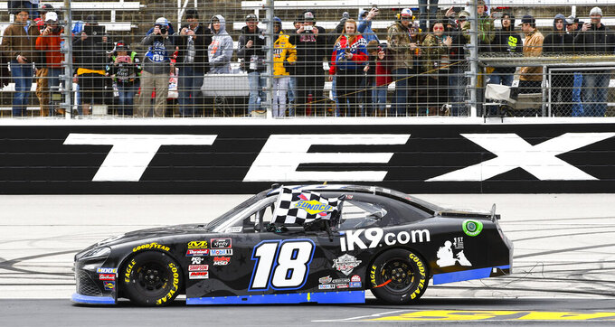 Kyle Busch celebrates with the checkered flag after winning a NASCAR auto race at Texas Motor Speedway, Saturday, March 30, 2019, in Fort Worth, Texas. (AP Photo/Larry Papke)