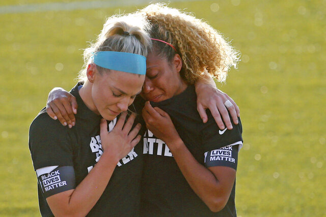 Chicago Red Stars' Julie Ertz, left, holds Casey Short after players for their team knelt during the national anthem before an NWSL Challenge Cup soccer match against the Washington Spirit at Zions Bank Stadium, Saturday, June 27, 2020, in Herriman, Utah. (AP Photo/Rick Bowmer)