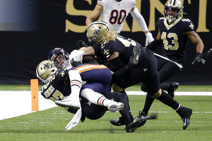 Chicago Bears tight end Cole Kmet is tackled on a reception by New Orleans Saints strong safety Malcolm Jenkins (27) and middle linebacker Alex Anzalone in the first half of an NFL wild-card playoff football game in New Orleans, Sunday, Jan. 10, 2021. (AP Photo/Butch Dill)