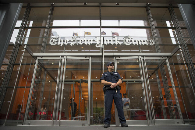 FILE - In this June 28, 2018, file photo, a police officer stands guard outside The New York Times building in New York. The campaign to reelect President Donald Trump sued The New York Times for defamation Wednesday, Feb. 26, 2020, saying it was responsible for an essay by a former executive editor for the newspaper that claimed the campaign made a deal with Russian officials to defeat Hillary Clinton in 2016. (AP Photo/Mary Altaffer, File)
