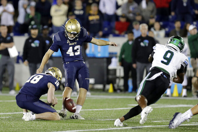Navy kicker Bijan Nichols (43), with holding J.R. Osborn, kicks a game-winning field goal as time expires during an NCAA college football game against Tulane, Saturday, Oct. 26, 2019, in Annapolis. Navy won 41-38. (AP Photo/Julio Cortez)