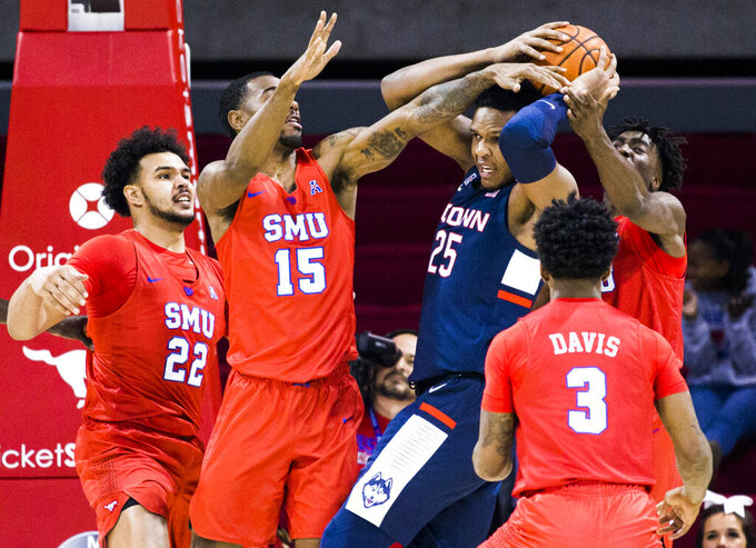 SMU players defend against Connecticut center Josh Carlton (25) during the first half of an NCAA college basketball game Wednesday, Feb. 12, 2020, in Dallas. (Ashley Landis/The Dallas Morning News via AP)