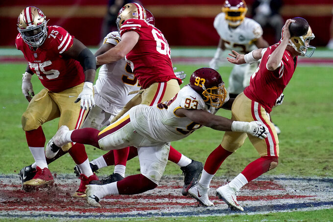 San Francisco 49ers quarterback Nick Mullens (4) manages to elude the tackle of Washington Football Team defensive tackle Jonathan Allen (93) during the second half of an NFL football game, Sunday, Dec. 13, 2020, in Glendale, Ariz. (AP Photo/Ross D. Franklin)