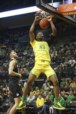 Oregon's Francis Okoro, right, dunks next to Montana's Mack Anderson during the first half of an NCAA college basketball game in Eugene, Ore., Wednesday, Dec. 18, 2019. (AP Photo/Chris Pietsch)