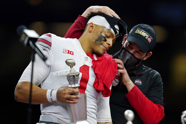 Ohio State head coach Ryan Day hugs quarterback Justin Fields after their win against Clemson in the Sugar Bowl NCAA college football game Friday, Jan. 1, 2021, in New Orleans. Ohio State won 49-28. (AP Photo/Gerald Herbert)