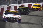 Denny Hamlin (11) leads Kurt Busch (1) and Joey Logano (22) into turn one during the NASCAR Cup series auto race in Richmond, Va., Saturday, Sept. 11, 2021. (AP Photo/Steve Helber)