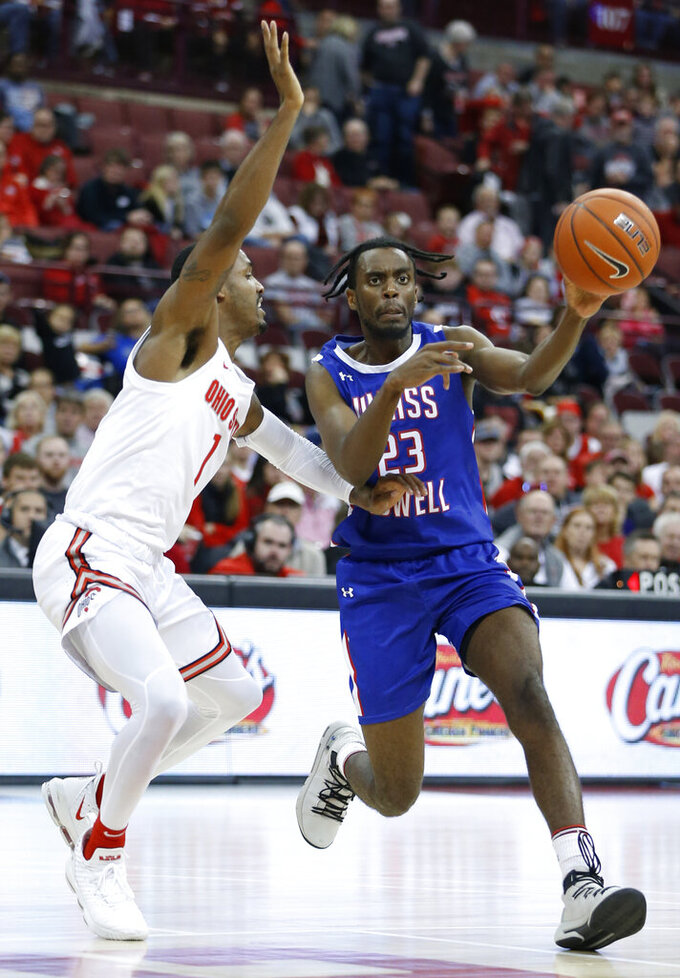 UMass-Lowell's Christian Lutete, right, passes the ball as Ohio State's Luther Muhammad defends during the first half of an NCAA college basketball game Sunday, Nov. 10, 2019, in Columbus, Ohio. (AP Photo/Jay LaPrete)