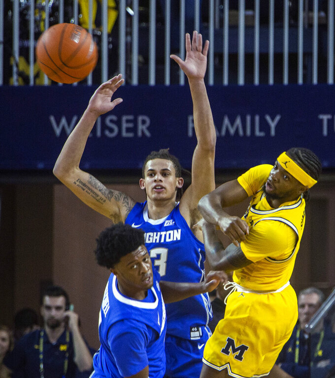 Michigan guard Zavier Simpson, right, passes the ball as Creighton guard Shereef Mitchell, bottom left, and forward Christian Bishop defend during the first half of an NCAA college basketball game at Crisler Center in Ann Arbor, Mich., Tuesday, Nov. 12, 2019. (AP Photo/Tony Ding)