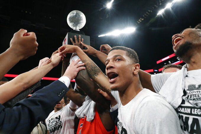 Auburn guard Samir Doughty, second from right, and his teammates celebrate with the trophy after defeating Richmond in an NCAA college basketball game in the Legends Classic, Tuesday, Nov. 26, 2019, in New York. (AP Photo/Kathy Willens)