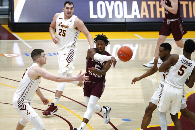 Southern Illinois guard Lance Jones, center, passes the ball through Loyola Chicago defenders during the first half of an NCAA college basketball game Friday, Feb. 26, 2021, in Chicago. (AP Photo/Shafkat Anowar)