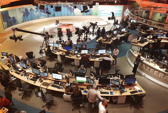 FILE - In this June 8, 2017 file photo, Al-Jazeera staff work at their TV station in Doha, Qatar. Dozens of journalists at Al Jazeera, the Qatari state-owned media company, have been targeted by advanced spyware in an attack attributed to the governments of Saudi Arabia and the United Arab Emirates, a cybersecurity watchdog reported on Sunday, Dec. 20, 2020. Citizen Lab, the watchdog, traced the malware that infected the personal phones of 36 journalists, producers, anchors and executives at Al Jazeera earlier this year back to the Israel-based NSO Group, which has been widely condemned for selling spyware to repressive governments.  (AP Photo/Malak Harb, File)