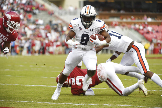 Auburn running back Shaun Shivers slips past Arkansas defenders to score a touchdown during the first half of an NCAA college football game, Saturday, Oct. 19, 2019 in Fayetteville, Ark. (AP Photo/Michael Woods)