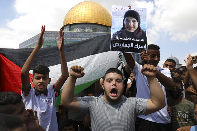 """Protesters hold a Palestinian flag and a placard of prisoner Israa Jaabis, who suffers from severe burns and is fighting for medical treatment, during a protest in support of Palestinian prisoners and the six who escaped this week, after Friday prayers at the Dome of the Rock Mosque in the Al Aqsa Mosque compound in in the Old City of Jerusalem, Friday, Sept. 10, 2021. Arabic reads: """"The Jerusalemite captive Israa Jaabis."""" (AP Photo/Mahmoud Illean)"""
