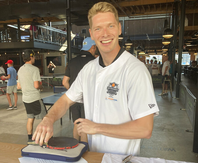 IndyCar driver and Tennessee native Josef Newgarden prepares to play in his charity ping pong tournament, Thursday Aug. 5, 2021 at Pins Mechanical Company in Nashville, Tenn. Newgarden won the tournament and hopes to take home a bigger trophy when IndyCar races Sunday through downtown Nashville.  (AP Photo/Daniel Gelston)