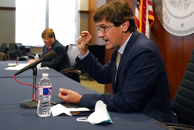 State health officer Dr. Thomas Dobbs explains how a person might react to a COVID-19 vaccination, right, during Gov. Tate Reeves' covid news briefing, Wednesday, Dec. 9, 2020 in Jackson, Miss. (AP Photo/Rogelio V. Solis)