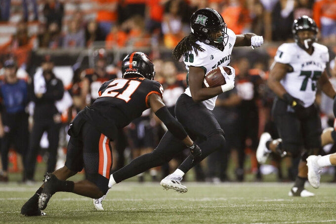 Oregon State defensive back Ron Hardge III, left, (21),  brings down Hawaii defensive back Nalu Emerson (28) during the second half of an NCAA college football game Saturday, Sept. 11, 2021, in Corvallis, Ore. Oregon State won 45-27. (AP Photo/Amanda Loman)