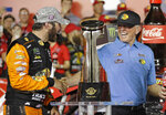 FILE - In this May 26, 2019, file photo, Martin Truex Jr., left, is congratulated by team owner Joe Gibbs in Victory Lane after winning the NASCAR Cup Series auto race at Charlotte Motor Speedway in Concord, N.C. NASCAR's season officially opens Sunday, Feb. 16, 2020, with the Daytona 500 at Daytona International Speedway. (AP Photo/Chuck Burton)