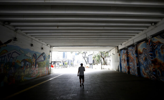 A man walks in a tunnel usually busy with pedestrians in the main business district in Jakarta, Indonesia, Friday, April 10, 2020. Mosques usually filled for Friday prayers and streets normally clogged with cars and motorcycles were empty as authorities in Indonesia's capital enforced stricter measures to halt the coronavirus' spread after deaths spiked in the past week. (AP Photo/Dita Alangkara)