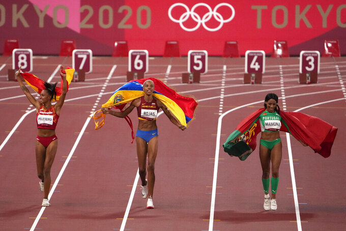 Gold medalist Yulimar Rojas of Venezuela, center, silver medalist Patricia Mamona of Portugal, right, and bronze medalist Ana Peleteiro of Spain, celebrate on the track following the final of the women's triple jump at the 2020 Summer Olympics, Sunday, Aug. 1, 2021, in Tokyo, Japan. (AP Photo/Charlie Riedel)