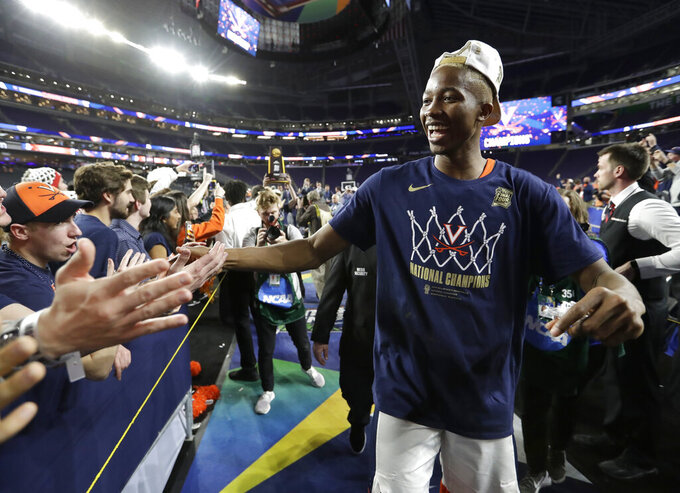 Virginia forward Mamadi Diakite celebrates with fans after the championship game against Texas Tech in the Final Four NCAA college basketball tournament, Monday, April 8, 2019, in Minneapolis. Virginia won 85-77 in overtime. (AP Photo/David J. Phillip)