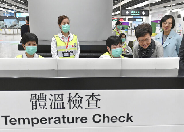 """In this Friday, Jan. 3, 2020, photo released by Hong Kong Government Information Service, Hong Kong Chief Executive Carrie Lam, second from right, accompanied by Secretary for Food and Health, Prof. Sophia Chan, right, reviews the health surveillance measures by officers of the Port Health Division at West Kowloon Station in Hong Kong. Hong Kong authorities activated a newly created """"serious response"""