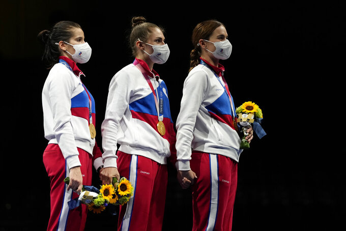 Hand by hand, gold medalists Russian Olympic committee Sabre team listen to the Russian Olympic Committee anthem during the medal ceremony for the women's Sabre team final medal competition at the 2020 Summer Olympics, Saturday, July 31, 2021, in Chiba, Japan. (AP Photo/Hassan Ammar)