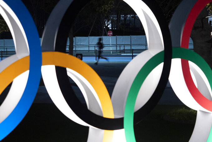 A man jogs past the Olympic rings Monday, March 30, 2020, in Tokyo. The Tokyo Olympics will open next year in the same time slot scheduled for this year's games. Tokyo organizers said Monday the opening ceremony will take place on July 23, 2021. (AP Photo/Jae C. Hong)