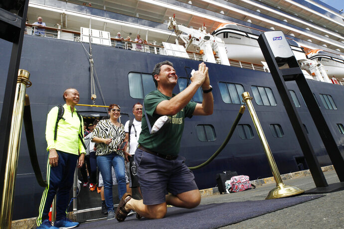 Passengers react after they disembarked from the MS Westerdam, back, at the port of Sihanoukville, Cambodia, Friday, Feb. 14, 2020. Hundreds of cruise ship passengers long stranded at sea by virus fears cheered as they finally disembarked Friday and were welcomed to Cambodia. (AP Photo/Heng Sinith)