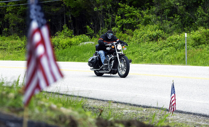 A motorcycle passes the scene of a fatal accident on Route 2 in Randolph, N.H., Saturday, June 22, 2019. Investigators pleaded Saturday for members of the public to come forward with information that could help them determine why a pickup truck hauling a trailer collided with a group of motorcycles on a rural highway. (Paul Hayes/Caledonian-Record via AP)