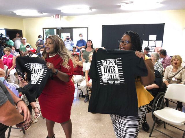 CORRECTS LAST NAME TO JAMES, NOT GAINES - Triana Arnold James, left, and Nselaa Ward hold up Black Lives Matter T-shirts as they protest a speech by U.S. Sen. Kelly Loeffler, Thursday, Sept 3, 2020, in Cumming, Ga. James and Ward kept Loeffler from finishing a campaign speech. (AP Photo/Jeff Amy)