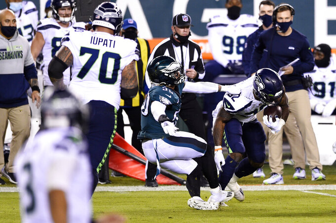 Philadelphia Eagles' Duke Riley (50) hangs onto Seattle Seahawks' Chris Carson (32) during the first half of an NFL football game, Monday, Nov. 30, 2020, in Philadelphia. (AP Photo/Derik Hamilton)