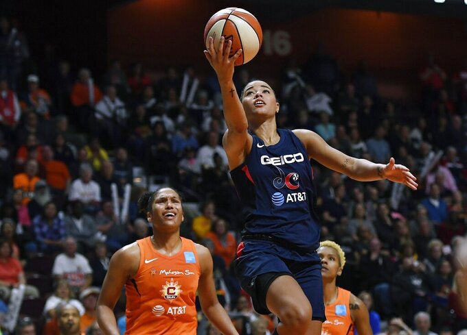 """FILE - Washington Mystics' Natasha Cloud drives to the basket past Connecticut Sun's Alyssa Thomas, left, and Courtney Williams, right, during the second half in Game 4 of basketball's WNBA Finals in Uncasville, Conn., in this Tuesday, Oct. 8, 2019, file photo. Point guard Natasha Cloud signed a multiyear contract to return to the Washington Mystics after opting out of last season to focus on bringing attention to social justice issues. """"She is the engine that drives us — our pace on offense, the start of our defense, the energy at practice on a daily basis,"""" Washington coach and general manager Mike Thibault said in the team's news release about the signing on Wednesday, March 10, 2021. (AP Photo/Jessica Hill, File)"""