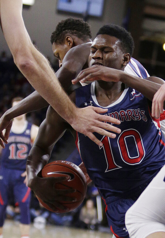 Saint Mary's forward Elijah Thomas (10) and Gonzaga guard Joel Ayayi scramble for the ball during the second half of an NCAA college basketball game in Spokane, Wash., Saturday, Feb. 9, 2019. Gonzaga won 94-46. (AP Photo/Young Kwak)