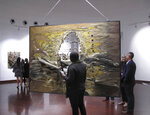 People inspect the work of South African abstract artist Christo Coetzee, who died in 2000 and is largely unknown in his home country, at the opening of a retrospective exhibition on Thursday, Oct. 4, 2018. The show at the Standard Bank Gallery in Johannesburg aims to stoke interest in Coetzee, who won some international acclaim decades ago. (AP Photo/Christopher Torchia)