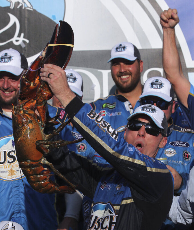 Kevin Harvick hoists a giant lobster in victory lane after winning a NASCAR Cup Series auto race at New Hampshire Motor Speedway in Loudon, N.H., Sunday, July 21, 2019. (AP Photo/Charles Krupa)