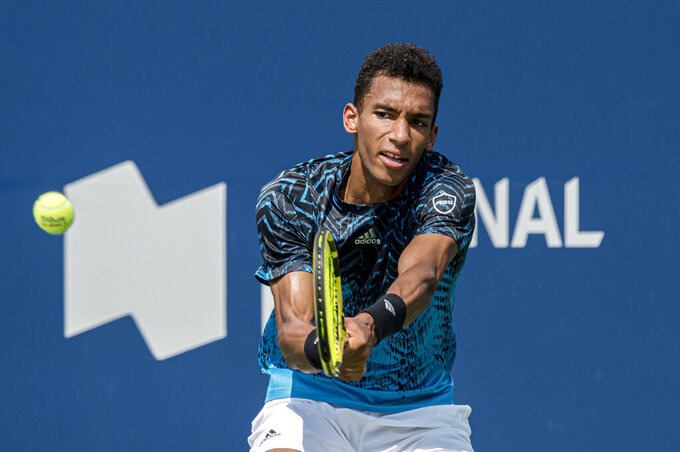 Canada's Felix Auger-Aliassime returns the ball to Serbia's Dusan Lajovic at the men's National Bank Open tennis tournament in Toronto, Wednesday, Aug. 11, 2021. (Christopher Katsarov/The Canadian Press via AP)