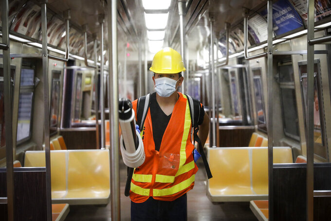 FILE - In this July 2, 2020, file photo, a contractor uses an electrostatic sprayer to disinfect subway cars to control the spread of COVID-19, in New York. The New York Metropolitan Transportation Authority has embarked on an aggressive cleaning and disinfecting program that will wind up costing it more than $1 billion, according to MTA officials. (AP Photo/John Minchillo, File)