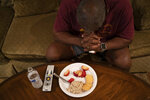 Mike Bishop prays before his dinner in front of the television in his living room in Byram, Miss., on Thursday, Oct. 8, 2020. He's hoping his wife, Bonnie Bishop, will be back by Thanksgiving. (AP Photo/Wong Maye-E)