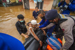 Rescuers assist an elderly man to climb into their boat at a flooded village in Banjar, South Kalimantan on Borneo Island, Indonesia, in this Saturday, Jan. 16, 2021 photo. Many thousands of people have been evacuated and a number have been killed in recent days in flooding on Indonesia's Borneo island, officials said Sunday. (AP Photo/Putra)
