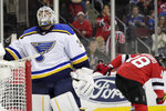 St. Louis Blues goaltender Jake Allen, left, looks on as New Jersey Devils right wing Drew Stafford (18) skates away after Stafford scored a goal against him during the second period of an NHL hockey game, Saturday, March 30, 2019, in Newark, N.J. (AP Photo/Julio Cortez)