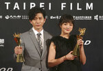 Taiwanese actress Gingle Wang, right, and Taiwanese actor Mo Tzu-yi hold their awards for Best Actress and Best Actor at the 2020 Taipei Film Festival in Taipei, Taiwan, Saturday, July 11, 2020. The 2020 Taipei Film Festival is the world's first large-scale film festival held by an entity after the outbreak of the COVID-19 epidemic. (AP Photo/Chiang Ying-ying)
