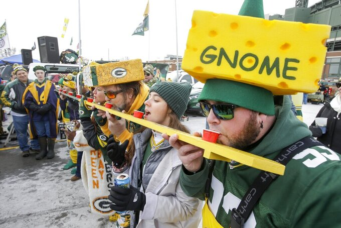 Fans do a shot outside Lambeau Field before an NFL divisional playoff football game between the Green Bay Packers and the Seattle Seahawks Sunday, Jan. 12, 2020, in Green Bay, Wis. (AP Photo/Mike Roemer)