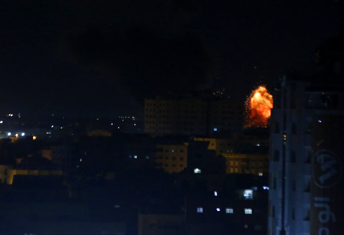 An explosion caused by Israeli airstrikes is seen on Gaza City, early Saturday, Oct. 27, 2018. Israeli aircraft struck several militant sites across the Gaza Strip early Saturday shortly after militants fired rockets into southern Israel, the Israeli military said. (AP Photo/Adel Hana)