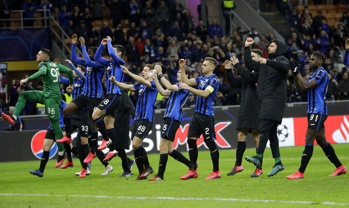 """FILE - In this Wednesday, Feb. 19, 2020 file photo, Atalanta players celebrate at the end of the Champions League round of 16, first leg, soccer match between Atalanta and Valencia at the San Siro stadium in Milan, Italy. It was the biggest soccer game in Atalanta's history and a third of Bergamo's population made the short trip to Milan's famed San Siro Stadium to witness it. Nearly 2,500 fans of visiting Spanish club Valencia also traveled to the Champions League match. More than a month later, experts are pointing to the Feb. 19 game as one of the biggest reasons why Bergamo has become one of the epicenters of the coronavirus pandemic — a """"biological bomb"""" was the way one respiratory specialist put it — and why 35% of Valencia's team became infected. The new coronavirus causes mild or moderate symptoms for most people, but for some, especially older adults and people with existing health problems, it can cause more severe illness or death. (AP Photo/Luca Bruno, File)"""