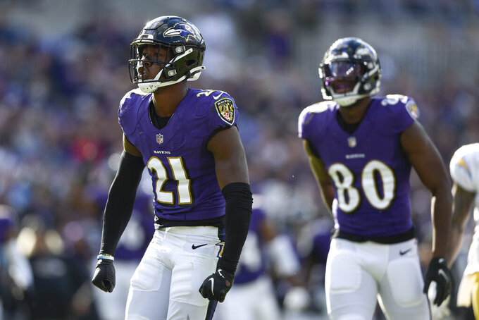 Baltimore Ravens' Brandon Stephens (21) and Miles Boykin (80) react after making a hit on Jalen Guyton, not visible, on a kickoff return during the second half of an NFL football game, Sunday, Oct. 17, 2021, in Baltimore. The Ravens won 34-6. (AP Photo/Gail Burton)